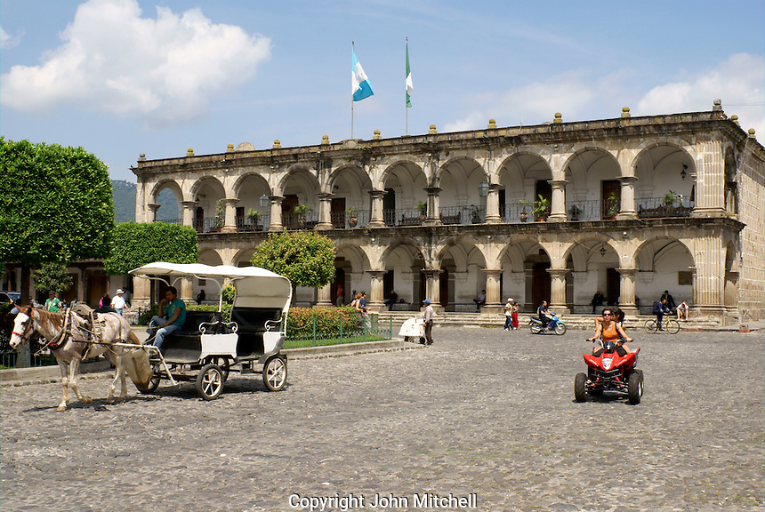 Horse and carriage and ATV in front of Palacio de Ayuntamiento or Town Hall facing the Parque Central, Antigua, Guatemala. Antigua is a UNESCO World heritage site....