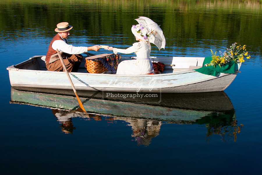 A victorian couple in a rowboat exchanging a letter