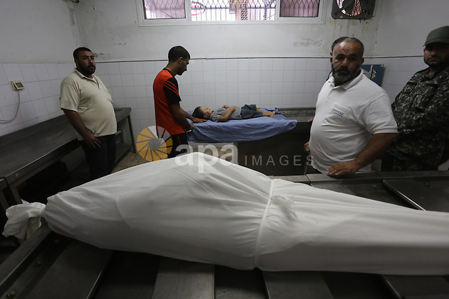 People stand around the body of a Palestinian woman who was killed after her house was brought down by an Israeli air strike in Gaza early on October 11, 2015. An Israeli air strike on a Hamas target in the Gaza Strip on Sunday brought down a nearby house killing a Palestinian woman and her daughter, hospital officials said, as a wave of violence in the region triggered fears of wider escalation. Photo by Mohammed Asad