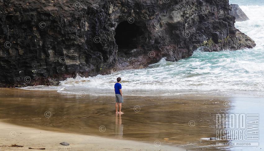 A hiker looks at rough surf by a sea cave at Hanakapi'ai Beach, reached by the Kalalau Trail, Kaua'i.