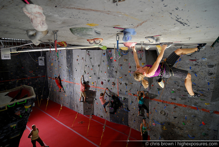 A woman climbs a ceiling in an indoor rock climbing gym.