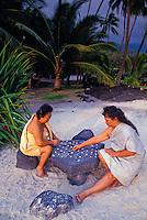 "Two woman playing Hawaiian checkers """" konane"""" at Puuhonua Honaunau, """"city of refuge"""", a national historical park on the Big island"