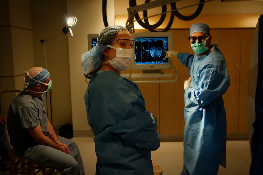 San Francisco, California, January 6, 2011 - University of California San Francisco neurologist Dr. Philip Starr MD, PhD (right) discusses real time brain scans with Dr. Alexander Papanastassiou (seated), a visiting doctor from the University Texas Health Science Center San Antonio, and Dr. Ellen Air (center), a visiting fellow, for patient Linda Sharpe during an iMRI surgery at University of California San Francisco Medical Center while. The SmartFrame(TM) Devices are used as guides to insert the electrodes into the desired point of the brain. By using real time MRI scans of the brain, the surgeon can find the optimal trajectory for the electrodes ensuring the safest path while also precisely locating the precise point...The MRI machine photographs the patient during the surgery allowing the doctors operating to view the procedure as well as support doctors and technicians to monitor from an outside room.  The iMRI procedure uses Deep brain stimulation (DBS), which has been used for over a decade to treat movement disorders such as Parkinson's disease, essential tremor, and dystonia. DBS uses a pulse generator implanted in the chest, similar to a pacemaker, to deliver pulses to specific regions of the brain via a permanently implanted electrode. In the U.S., DBS is normally done while the patient is awake, because the surgeon needs to induce the symptoms (like the involuntary movements of Parkinson's) to know if he's in the right place, and if the patient is unconscious, the symptoms can't be induced. Many patients find it hard to tolerate. Their head is clamped in a frame, they're aware of their surroundings, and the surgeon is deliberately producing tremors and twitches while they lie there...Interventional MRI (or iMRI) allows surgeons to implant these electrodes while the patient is unconscious taking advantage of MR imaging in real time by performing procedures inside the scanner itself. Doctors Paul Larson MD, and Philip Starr MD, PhD were both involved with
