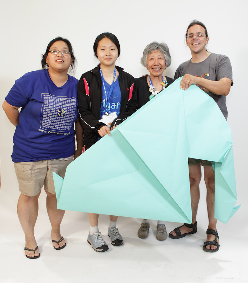 The oversized folding event. Team Flexible Flappers fold an origami creation titled Easyphant / Swan designed by unknown. Team members (left to right): Linda Yau, Seryung Park, Patsy Wang-Iverson, Malachi Brown