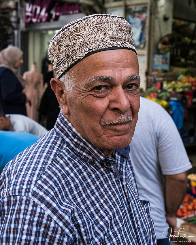 A Palestinian Arab man wearing an ornately decorated taqiyah or skull cap.  Many Muslim men wear the taqiyah to emulate Mohammed, who always had his head covered.  Jerusalem, Israel.