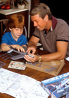 Father and son enjoy the fun of building a model airplane at hom