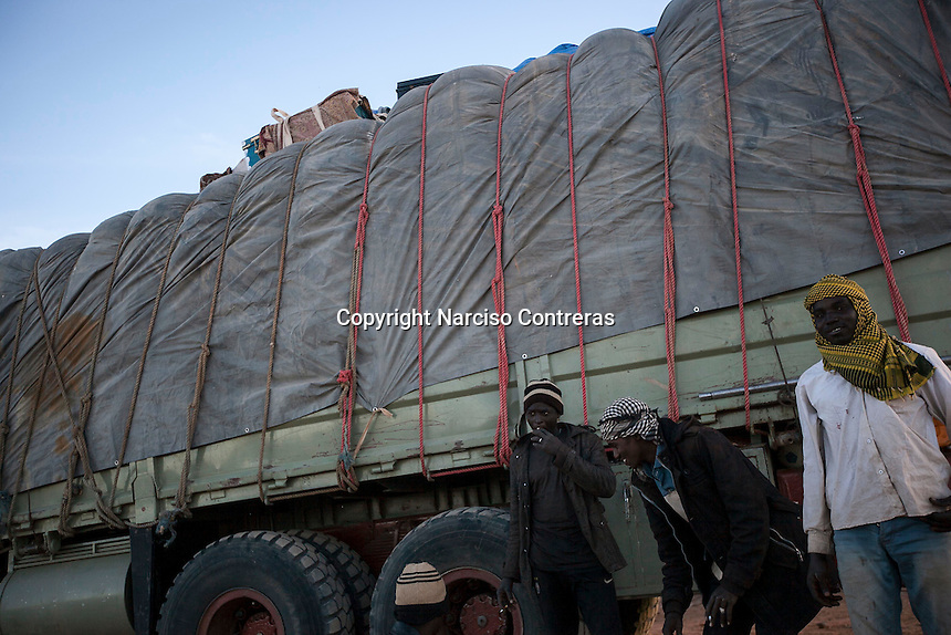 November 22, 2014 - Murzuq region, Libya: Sub-Saharan migrants are seen along a truck heavily loaded with goods at a black market area in the middle of the desert as they head to the border in Southwest Libya. Libya's revenues from smuggling trade including human trafficking is up to 10% of the national GDP, making this one of the most profitable illegal business across the country. In spite of the international concern of human rights violations, Sub-Saharan migrants risk their lives across Libya, often jailed, sold and kidnapped during their hazardous trip through the Sahara desert to the coastal ports as most of them attempt to reach Europe. (Photo/Narciso Contreras)