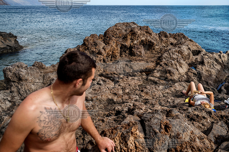 Tourists sunbathe on the volanic rock  that makes up the shore line in Tacoron. /Felix Features
