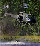 A Bell UH-1 helicopter, operatied by Lundsford Air Consulting Inc., fliles across a lake at the Flagler County Airport dragging a firefighting bucket beneath, Monday, Oct. 15, 2004.  The helicopter was on a training flight to instruct pilots and crewmembers, of the Air Force of the Dominican Republic, in the use of airborne firefighting equipment as well as search and rescue tecniques.(Brian Myrick)
