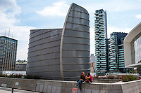 Milano, quartiere Porta Nuova Garibaldi. Due ragazze sedute presso una struttura metallica in piazza Gae Aulenti. Sullo sfondo a dx: la Torre Solaria alle Varesine --- Milan, Porta Nuova Garibaldi district. Two girls sitting by a metal structure in Gae Aulenti square. On the background: the Solaria Tower at the Varesine