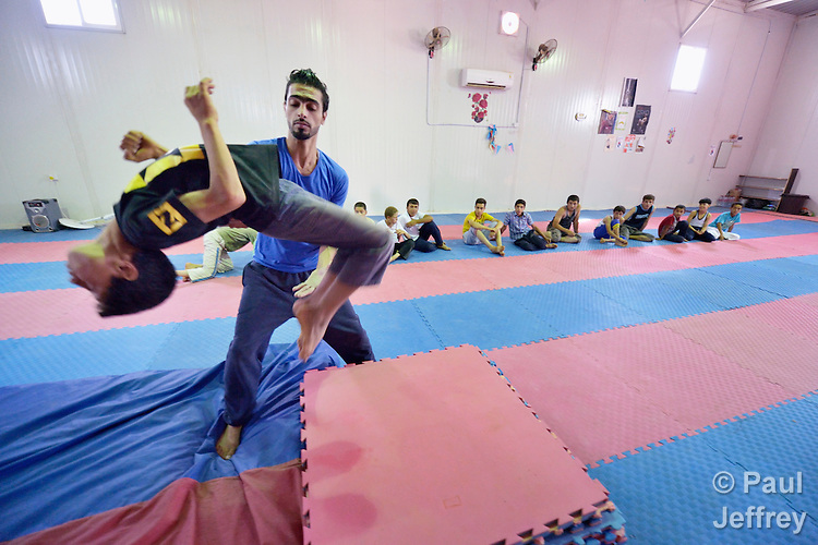 Boys learn gymnastics and circus skills as part of a psycho-social program run by Finn Church Aid in the Zaatari refugee camp near Mafraq, Jordan. Established in 2012 as Syrian refugees poured across the border, the camp held more than 80,000 refugees by early 2015, and was rapidly evolving into a permanent settlement. Finn Church Aid is a member of the ACT Alliance, which provides a variety of services to refugees living in the camp.