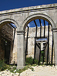 An old stone arch entrance to a derelict building