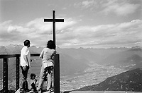 Switzerland. Canton Ticino. Monte Tamaro. A couple with their children stands by the chapel Santa Maria degli Angeli which offers an unique viewing terrace and a large panorama on the swiss Alps. The chapel Santa Maria degli Angeli was build the swiss well-known Ticinese architect Mario Botta. Monte Tamaro is a mountain reaching a height of 1,962 metres. 25.06.06 © 2006 Didier Ruef