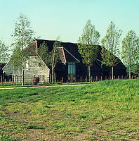 The exterior of the wood clad barn seen from across the field