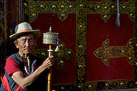 An old man and his prayer wheel, near Barkhor street leaning against a traditional doorway in Lhasa,