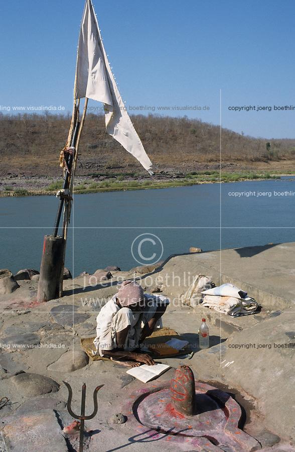 INDIA Madhya Pradesh Omkareshwar, Hindu pilgrim at the holy Narmada river, in front Trident and Shiva Lingam symbol of god shiva / INDIEN Madhya Pradesh Omkareshwar, Hindu Pilger liest aus einem Religions Buch am heiligen Fluss Narmada , im Vordergrund der Trident Dreizack und Shiva Lingam ein Phallus Symbol beides Symbole des Gott Shiva