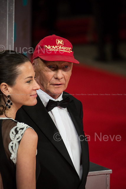 Niki Lauda (Former Formula One racing driver) &amp; Birgit Wetzinger (Niki Lauda wife).<br /> <br /> London, 16/02/2014. Red Carpet of the 2014 EE BAFTA (British Academy of Film and Television Arts) Awards Ceremony, held at the Royal Opera House in London.
