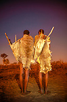 Two San men dressed in traditional skins stand against the post-sunset glow in Botswana's Kalahari Desert.