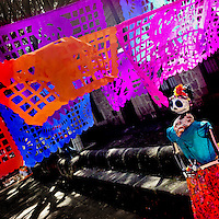 A female skeleton figure, representing a Mexican cultural icon called La Calavera Catrina, is seen under the papel picado banners on the street during the celebrations of the Day of the Dead (Día de Muertos) holiday in Morelia, Michoacán, Mexico, 2 November 2014.