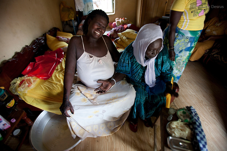 July 18, 2011 - Juba, Republic of South Sudan - Lushi Rashid (L), a 29 year old muslim South Sudanese woman, cries as the contractions grow stronger during the birth of her fifth child at her family home with the help of her aunt (R) and Regabia Ahmad (C), a qualified birth attendant, in Juba, the capital city of South Sudan. Regabia has been delivering babies in South Sudan for over twenty years. she was trained by the health ministry and works at a local primary health clinic. With fewer than 100 trained midwives for a population of over eight million, South Sudan has the highest maternal mortality rate in the world.  One in seven South Sudanese women is likely to die because of complications from delivery. Just 10 per cent of South Sudanese women have access to medical professionals during childbirth. Photo credit: Benedicte Desrus