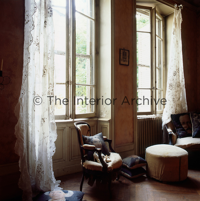 Two period armchairs are set in front of tall casement windows dressed with sheer fabrics.