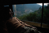 A man lays by a window in a sleeper bus in rural Yunnan Province, China.