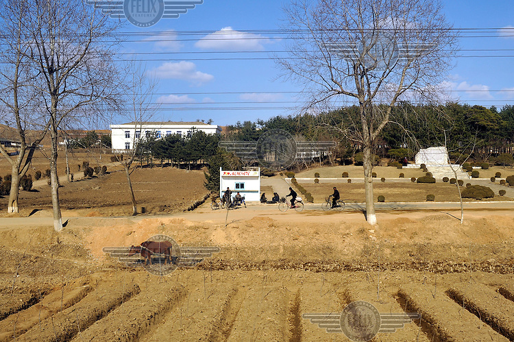 Cyclists ride on a rural road past fields prepared for the new season, as seen from a train travelling from the Chinese border to Pyongyang.