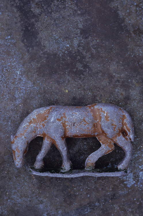 Battered lead model of grazing horse lying on tarnished metal