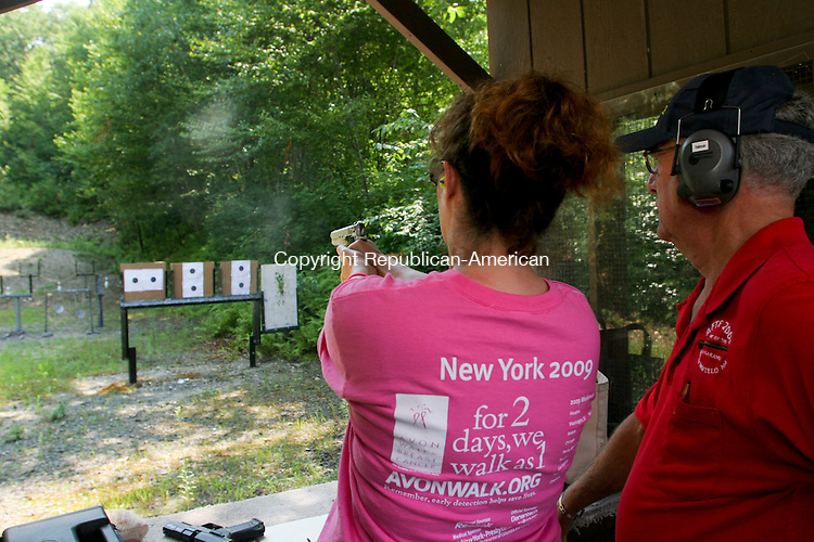 WOLCOTT, CT 17 JULY 2010 - 0717JW09.jpg --  Kathleen O'Donnell of Waterbury fire a 9mm hand gun for the first time while being coached by Wolcott Land Owners Protective Association Vice President Marshall Robinson Saturday morning during the 3rd annual shoot and silent auction to raise money for Breast Cancer walk that O'Donnell will be a part of and to start an Emergency Relief Fund. Approximately 8 thousand dollars was raised according to club Board of Directors member Frank Noble. Jonathan Wilcox Republican-American