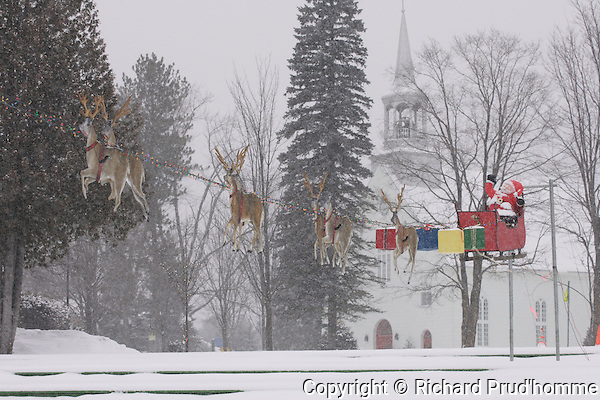 Santa Claus in his sleigh with his raindeers flying over the town of Saint-Alphonse-Rodriquez, Quebec