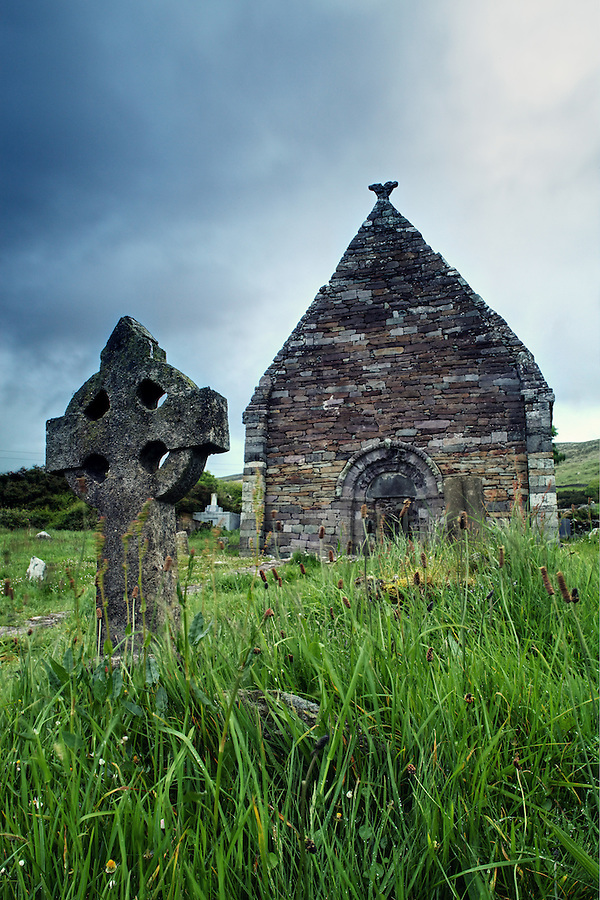 A cross headstone stands in front of ruined Norman church of Kilmalkedar (Cill Mhaoilcheadair), Dingle Peninsula, County Kerry, Republic of Ireland