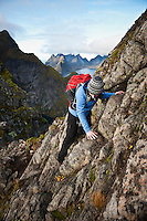 Female hiker climbs rocks near summit of Reinebringen, Moskenesoy, Lofoten Islands, Norway