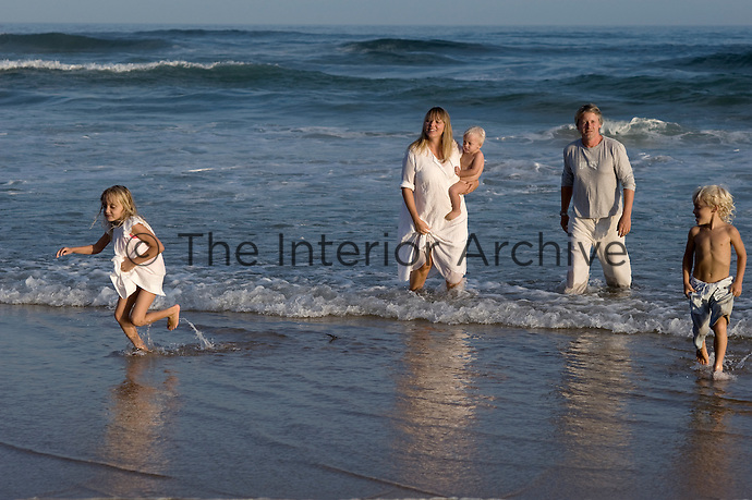 Trevyn McGowan and her family frolick on the shore infront of their home