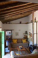 Double green doors open into the guest house living room which has a beamed double height ceiling and a contemporary wood burning stove
