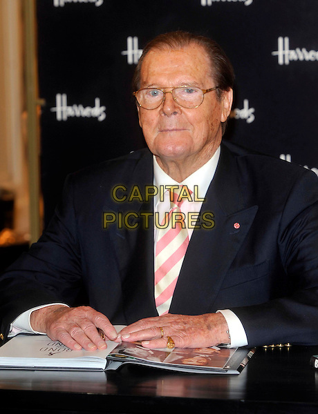 Sir Roger Moore.Photocall for the book signing of 'Bond On Bond', Harrods, Knightsbridge, London, England..11th October 2012.book half length table sitting glasses white shirt pinks stripe tie black blue suit jacket.CAP/ROS.©Steve Ross/Capital Pictures