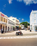 BERMUDA, Hamilton, woman riding scooter on street with buildings in the background