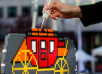 LEGO brick artist Nathan Sawaya puts the finishing touches on a Wells Fargo stagecoach artwork during the Wells Fargo Community Celebration, held October 29, 2011 in downtown Charlotte NC. The daylong festival took place in the streets, in public atriums and in downtown museums, which offered free admission all day long. Wells Fargo, which this month completed its conversion from Wachovia, picked up the bill.