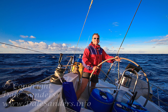 Man at the helm of a sailboat, sailing in the wide open ocean.  Dale Sanders,  sailing  across the Pacific Ocean from Hawaii to California.   Model Released