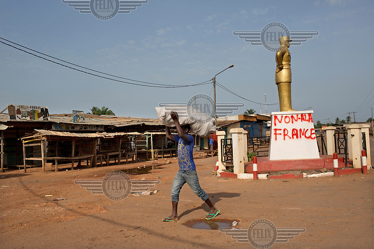 A man carries a sack of goods on his head through the Muslim district PK5. Behind him, on a statue's plinth, is anti-French graffiti, some of the population blame the French for not intervening earlier to protect them from Anti-Balaka vigilantes.In late 2012 after years of instability and conflict, the Seleka, a predominantly Muslim rebel group, fuelled by grievances against the government, overran the country and, In March 2013, ousted President Francois Bozize, who fled the country. The rebel's leader Michel Djotodia was proclaimed president in August 2013. He disbanded the Seleka in September 2013 but law and order collapsed and ex-Seleka fighters roamed the country committing atrocities against the civilian population. In an attempt to defend their lives and property vigilante groups, calling themselves Anti-Balaka (Anti-Machete), formed to confront the ex-Seleka fighters but soon began to take reprisals against the wider Muslim population and the conflict became increasingly sectarian. By December 2013, with international fears of a genocide being voiced, French led peacekeepers deployed to the country began to act on a UN mandate to disarm the fighters and protect the civilian population. However, they have struggled to contain the situation. Much of the Muslim population, in particular, have been forced into ghettos where they are suffering from food shortages and limited access to healthcare. Often, only a few peacekeepers stand between them and a massacre by vengeful Anti-Balaka militants. UN reports describe 'thousands' killed, while over 600,000 people have been internally displaced and a further 200,000 have fled the county.