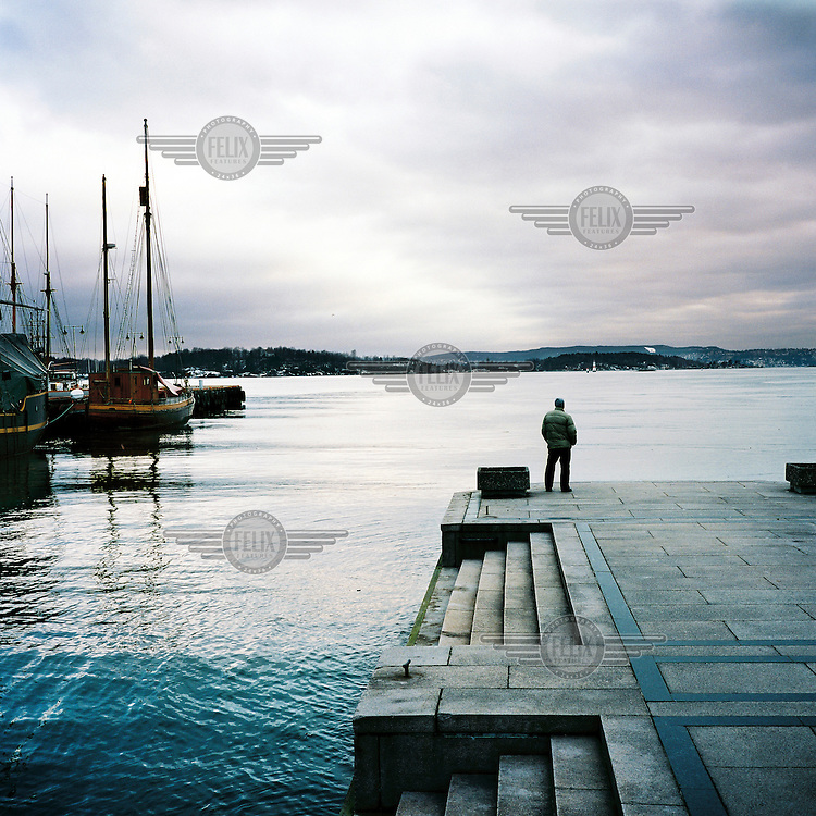 A man looks out over the harbour in Oslo.