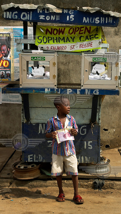 A boy stands under a pair of ballot boxes on election day. Nigeria has been a democracy since 1999.