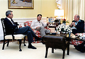 United States President Ronald Reagan, center, meets with National Security Advisor Frank Carlucci, left, and U.S. Secretary of State George Shultz, right, in the White House Residence in Washington, D.C. on Sunday, October 25, 1987.  The two men reported to the President on their recent meetings in Moscow..Mandatory Credit: Mary Anne Fackelman-Miner - White House via CNP
