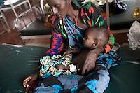 Kenya - Dadaab – 22nd July 2011. Somali refugee at GIZ Hospital inside the refugee camp where her child is being cured for severe malnutrition.