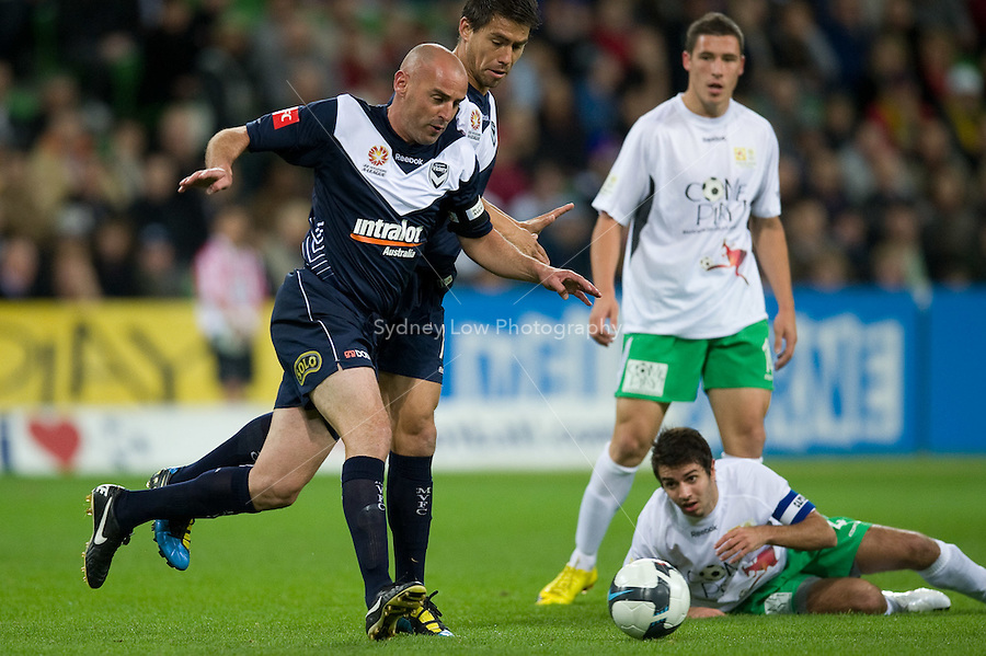 MELBOURNE, AUSTRALIA - May 14, 2010: Kevin Muscat from Melbourne Victory runs with the ball in Kevin Muscat Testimonial match between the Melbourne Victory and Come Play XI at AAMI Park on May 14, 2010 in Melbourne, Australia. Photo Sydney Low www.syd-low.com