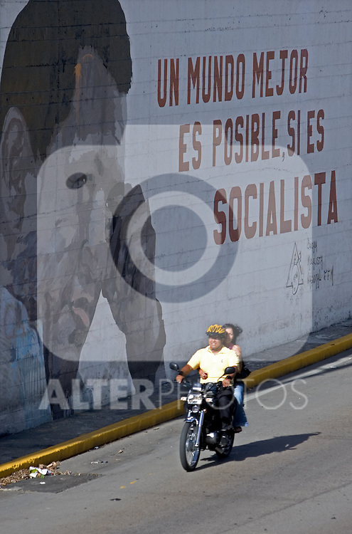 "A motorcycle passes by a wall painting with the face of Venezuelan President Hugo Chavez  with a phrase reading ""a better world is possible, if it's socialist"" in Caracas, Venezuela, on Saturday, Jul. 08, 2006. (ALTERPHOTOS/Alvaro Hernandez)"