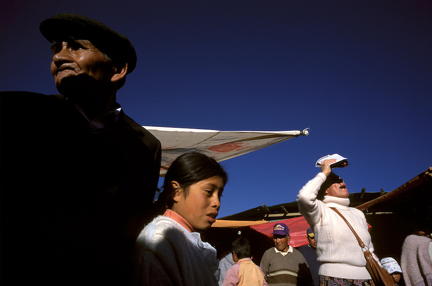 """Shouting into the evening sun, a Bolivian radio evangelist chides Paceños on their way to the central cemetery in La Paz to celebrate the Day of the Dead. Evangelical preachers campaign against many of the traditional cultural events with origins in Catholicism or local indigenous religions as being """"demonic."""""""