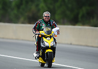 Mar. 10, 2012; Gainesville, FL, USA; NHRA funny car driver John Force rides his scooter during qualifying for the Gatornationals at Auto Plus Raceway at Gainesville. Mandatory Credit: Mark J. Rebilas-