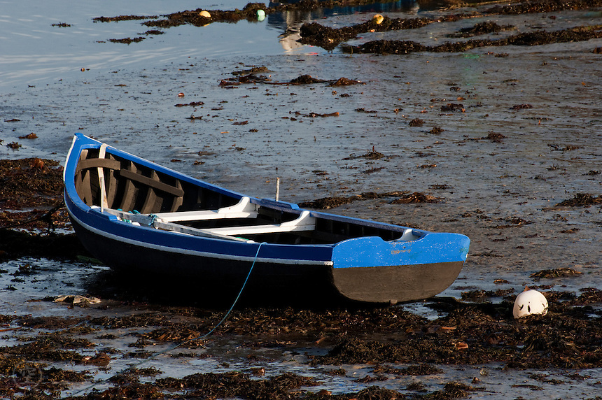 A boat in Spiddal harbour at low tide, Ireland.