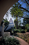 Mission San Diego de Alcala founded in 1769 white washed bell tower in back coutyard with sculpture of priest holding rosary San Diego California USA