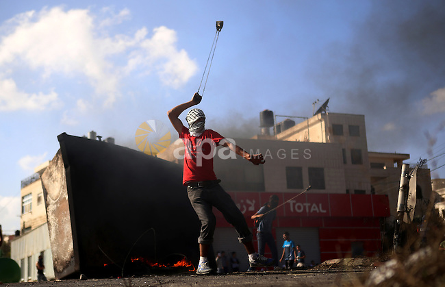 A Palestinian protester uses a sling shot to throw stones at Israeli security forces during clashes near the Jewish settlement of Bet El, near the West Bank city of Ramallah, on October 14, 2015. Seven Israelis and 30 Palestinians, including children and assailants, have been killed in two weeks of bloodshed in Israel, Jerusalem and the occupied West Bank. The violence has been partly triggered by Palestinians' anger over what they see as increased Jewish encroachment on Jerusalem's Al-Aqsa mosque compound. Photo by Shadi Hatem